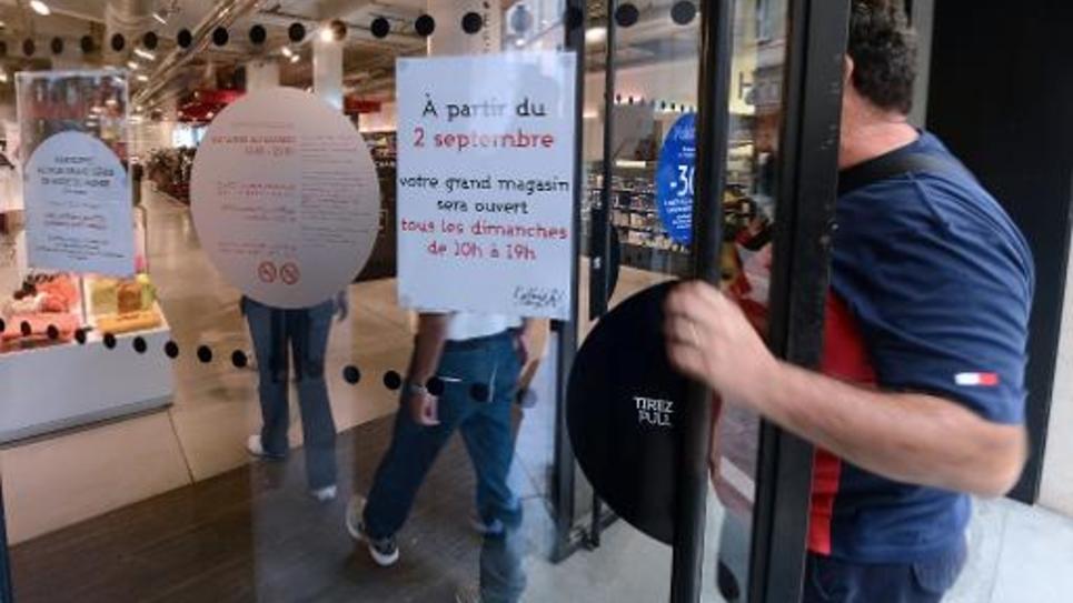 Des personnes entrent dans un magasin ouvert le dimache