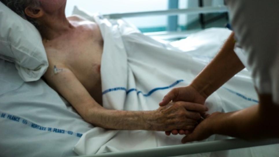 Une infirmière au chevet d'un patient dans une unité de soins palliatifs d'Argenteuil, le 22 juillet 2013
