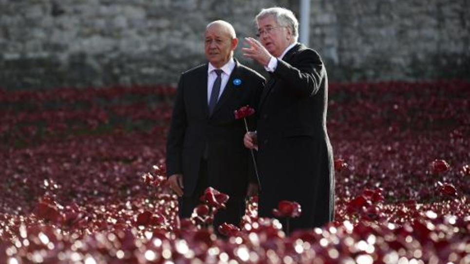 Le ministre français de la Défense Jean-Yves Le Drian (g) avec son homologue britannique Michael Fallon (d) au milieu des coquelicots de céramique dans les douves de la Tour de Londres le 10 novembre 2014