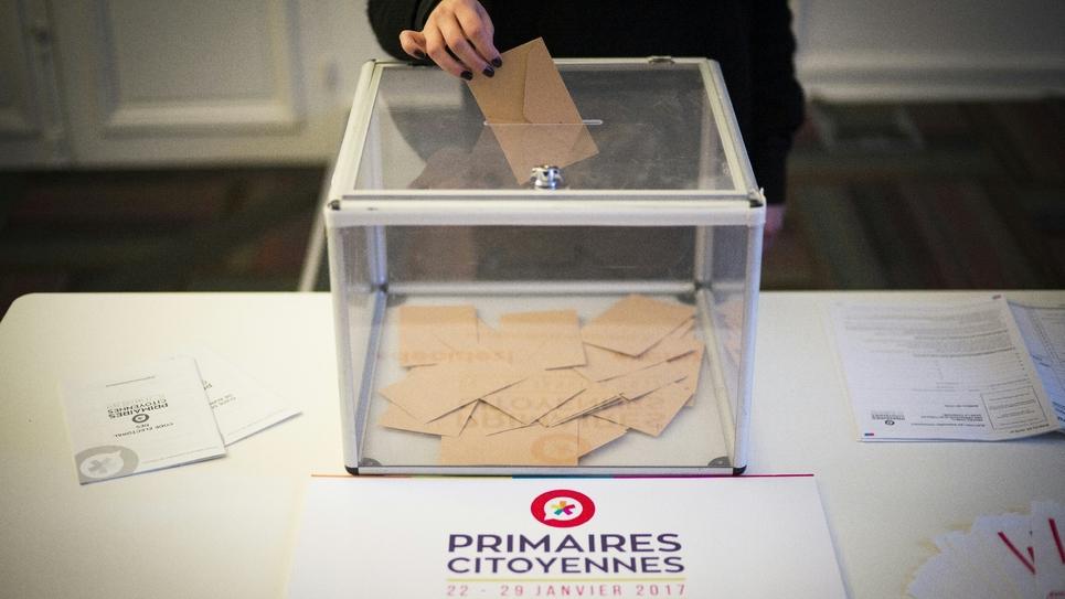 Une électrice dépose son bulletin dans l'urne au premier tour de la primaire socialiste élargie le 16 janvier 2017 à Paris