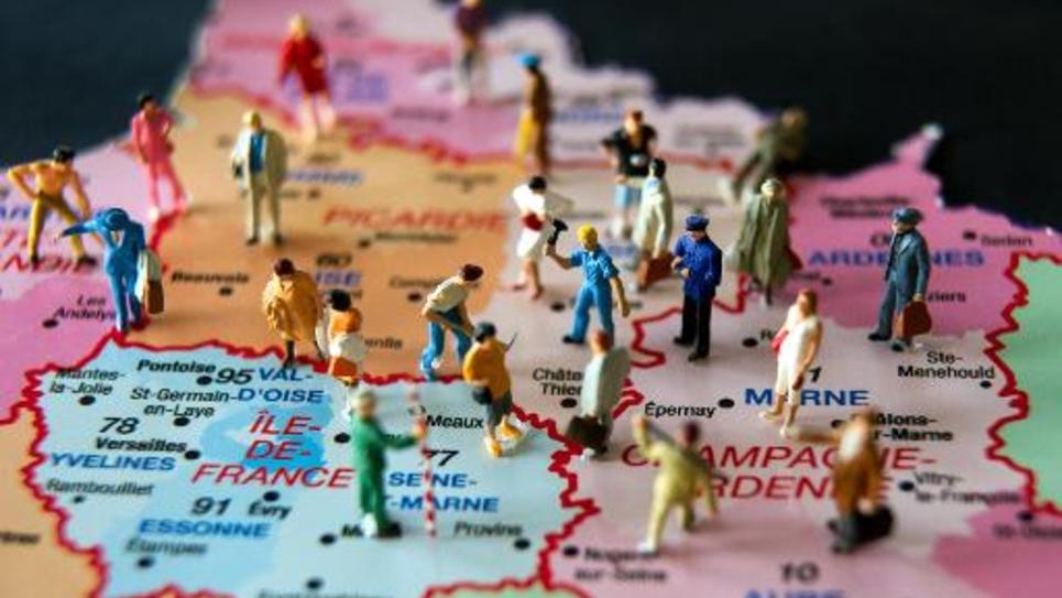 Des figurines sur une carte de France illustrant la réforme territoriale