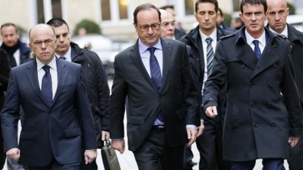 François Hollande est entouré par le ministre de l'Intérieur Bernard Cazeneuve (G) et le Premier ministre Manuel Valls, le 9 janvier 2015 à Paris