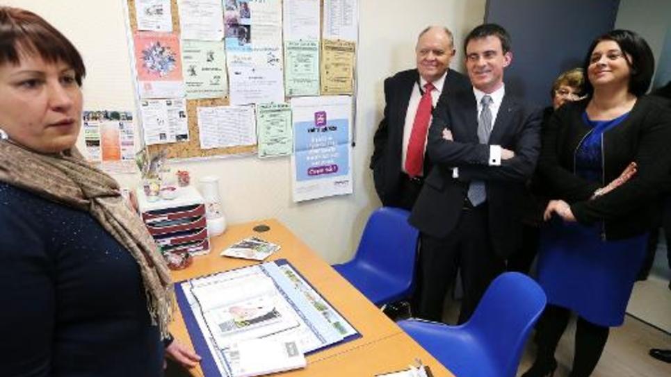 Le Premier ministre Manuel Valls (c) et la ministre du Logement, Sylvia Pinel (d) visitent le 13 mars 2015 la maison des services publics de la ville de Vailly-sur-Aisne, dans l'Aisne