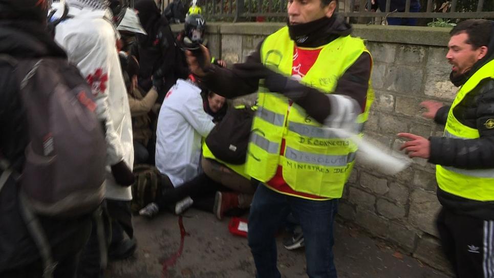 """Capture réalisée à partir d'une vidéo de l'AFP TV montrant des """"street-medics"""" portant secours à un """"gilet jaune"""" (caché) qui vient d'avoir la main arrachée par une grenade lancée par des gendarmes lors de vives tensions devant l'Assemblée nationale, le 9"""
