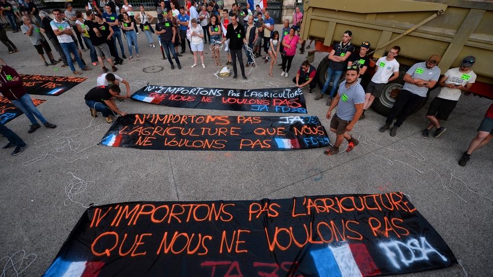 Des agriculteurs étendent des bannières pendant une manifestation contre l'accord UE-Mercosur le 2 juillet 2019 au Mans