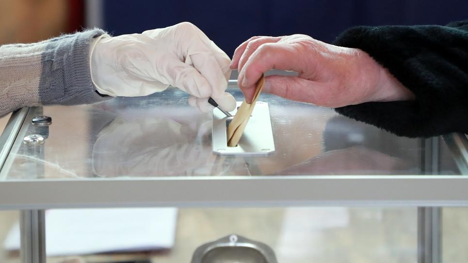Dans un bureau de vote au Touquet, où l'assesseur porte des gants, le 15 mars 2020