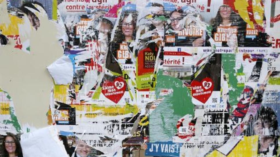 Des affiches électorales superposées et arrachés se disputent un mur de Bobigny, le 22 mars 2015 au 1er tour des départementales