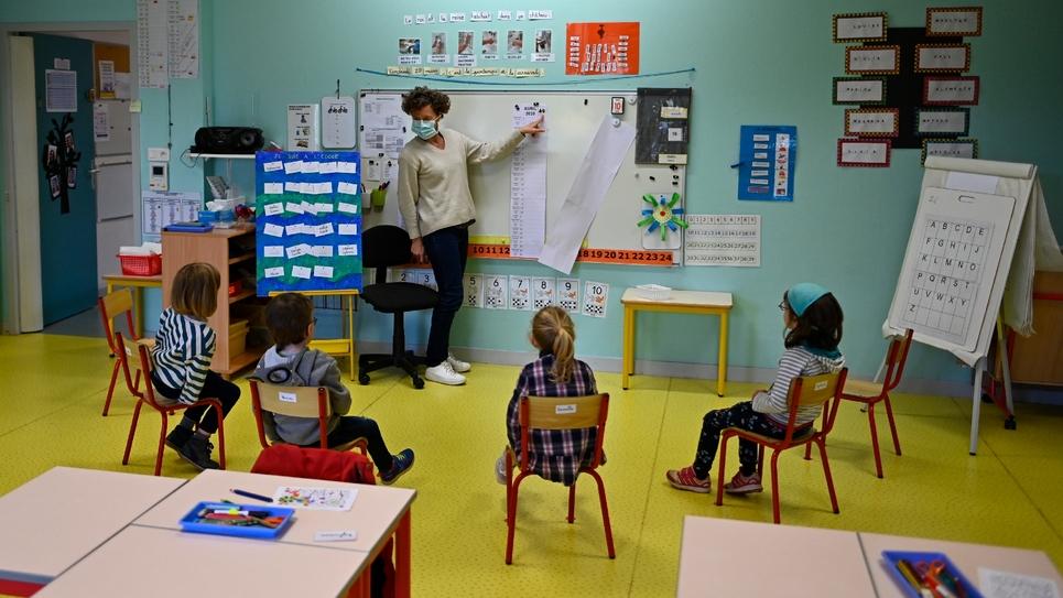 Une enseignante porte un masque de protection et se tient à distance de ses élèves, au premier jour de leur retour en classe, le 12 mai 2020 à Bruz, près de Rennes