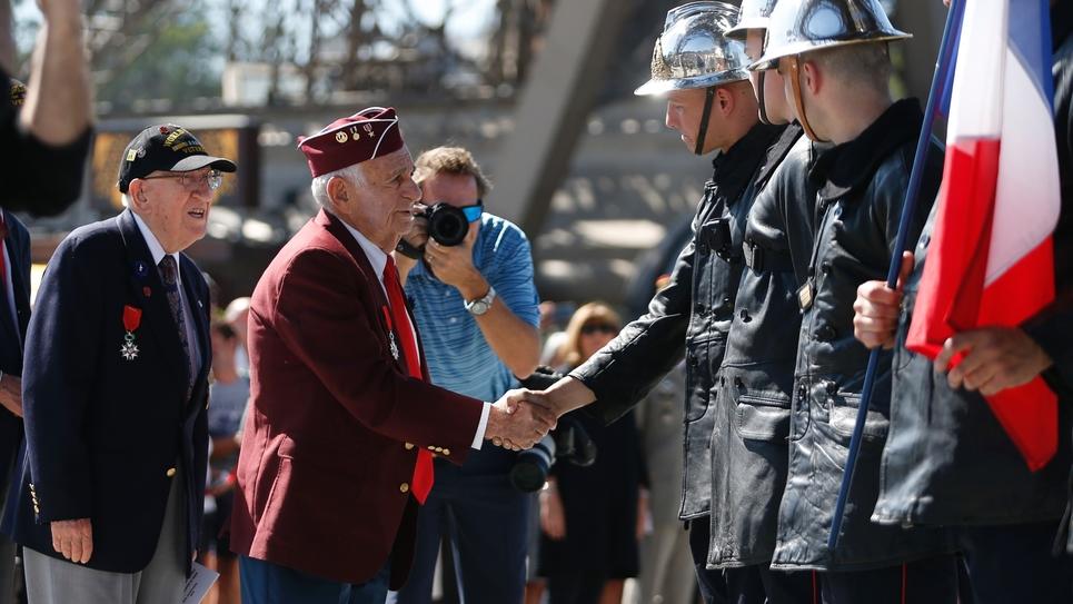Un vétéran salue des pompiers le 25 août 2019 lors de la cérémonie d'hommage à leurs collègues qui ont hissé l'étendard français 75 ans plus tôt sur la Tour Eiffel
