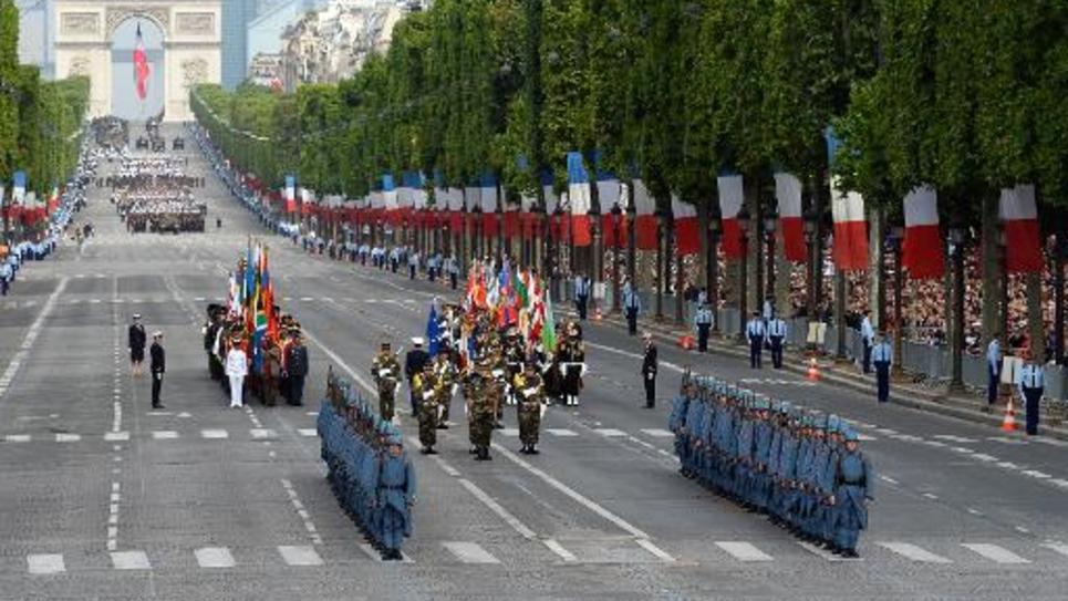 """Des soldats portant l'uniforme bleu des """"Poilus"""" de la première guerre mondiale, défilent sur Champs Elysées le 14 juillet 2014 à Paris"""
