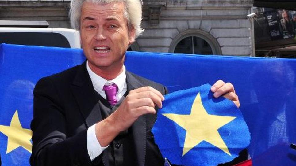 """Le dirigeant du groupe populiste néerlandais abti immigrés, et anti Islam, Geert Wilders a """"symboliquement"""" découpé une étoile dorée sur un drapeau de l'UE mardi à Bruxelles pour, selon lui, indiquer que les Pays-bas souhaitent quitter l'UE"""