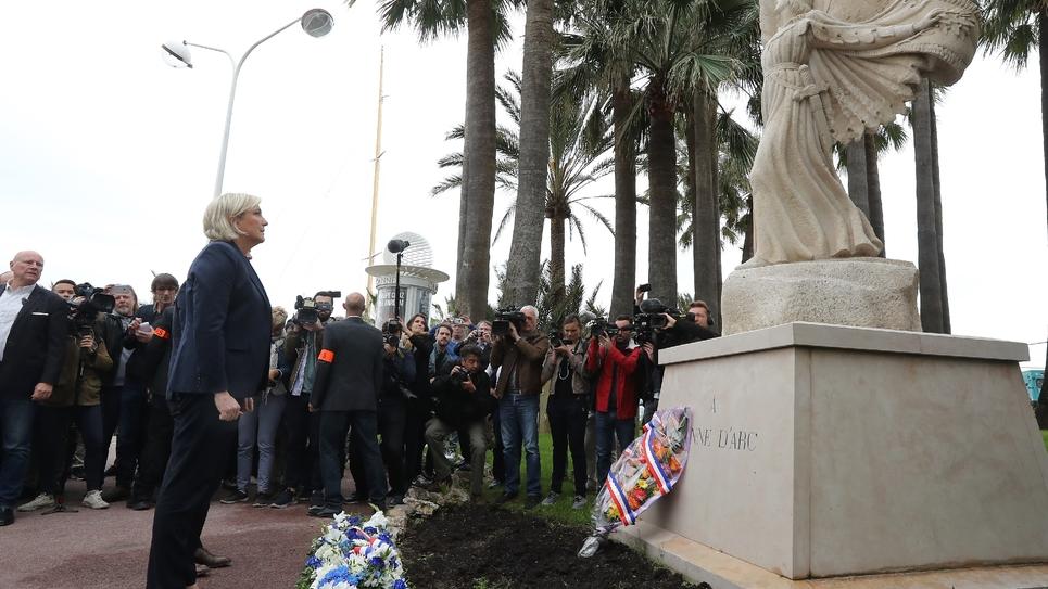 """La présidente du Front national  Marine Le Pen dépose une gerbe """"A Jeanne pour la France"""" au pied d'une statue de Jeanne d'Arc le 1er mai à Cannes (Alpes-Maritimes)"""