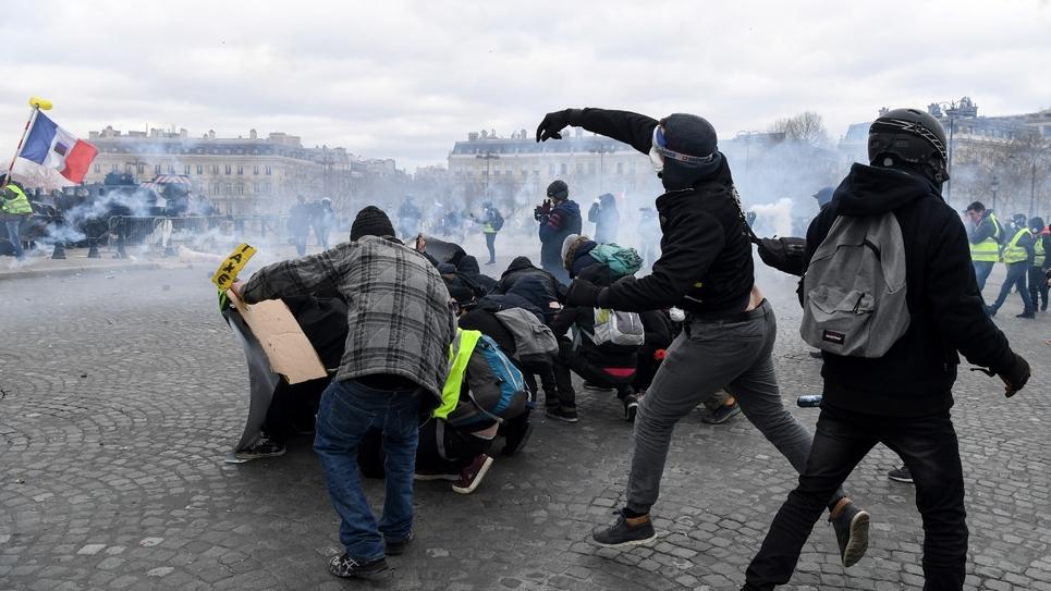 Des manifestants jettent des pavés sur les forces de l'ordre Place de l'Etoile à Paris, le 16 mars 2019