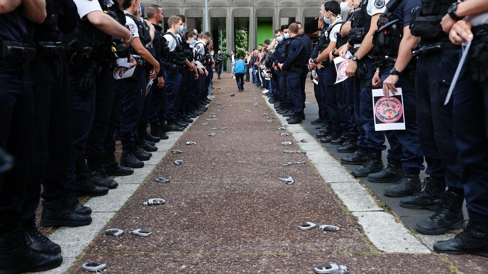 Des policiers ont déposé posé leurs menottes et brassards par terre lors d'un rassemblement devant la préfecture de Seine-Saint-Denis, à Bobigny, le 11 juin 2020, pour protester contre les dernières annonces du ministre de l'Intérieur