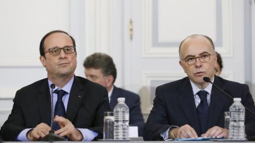Le président François Hollande (g) et le ministre de l'Intérieur Bernard Cazeneuve le 9 janvier 2014 lors d'une réunion de crise à Paris