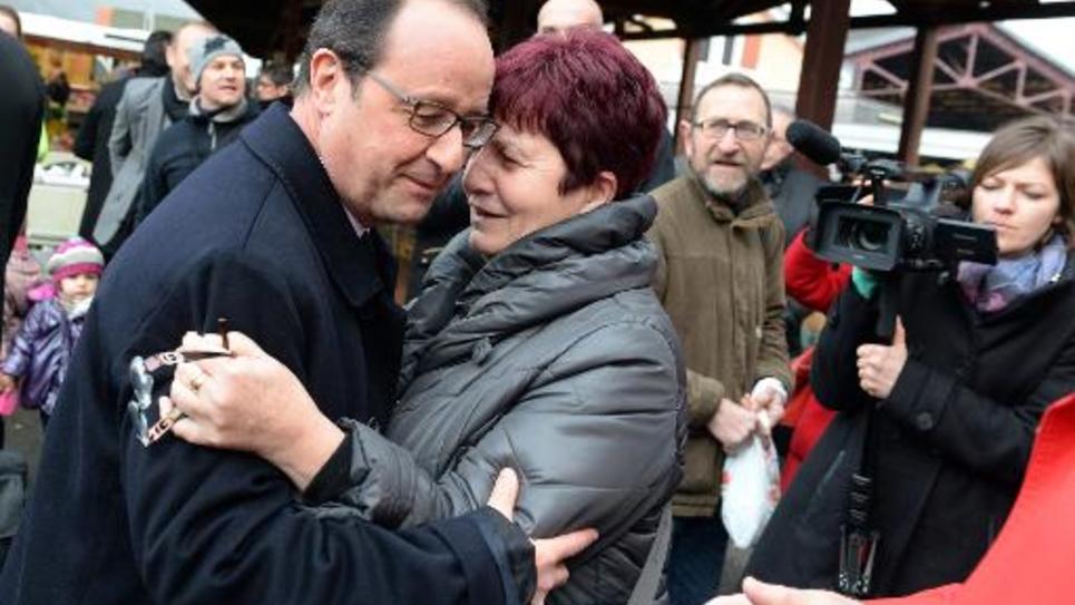 François Hollande prend une femme dans ses bras sur le marché de Tulle, le 17 janvier 2015