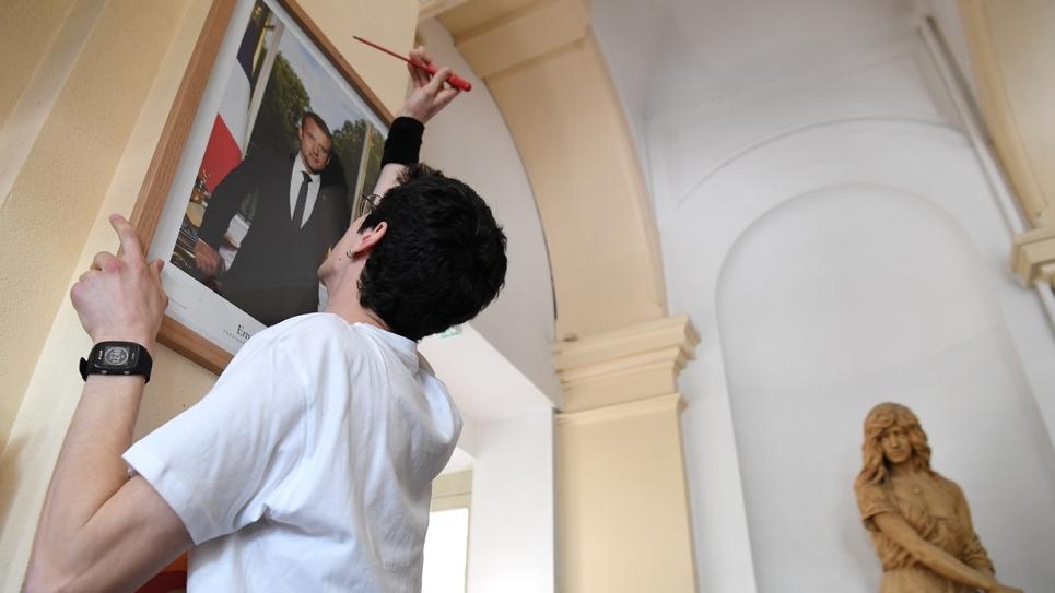 Un militant décroche un tableau d'Emmanuel Macron dans la mairie du XIXe à Paris