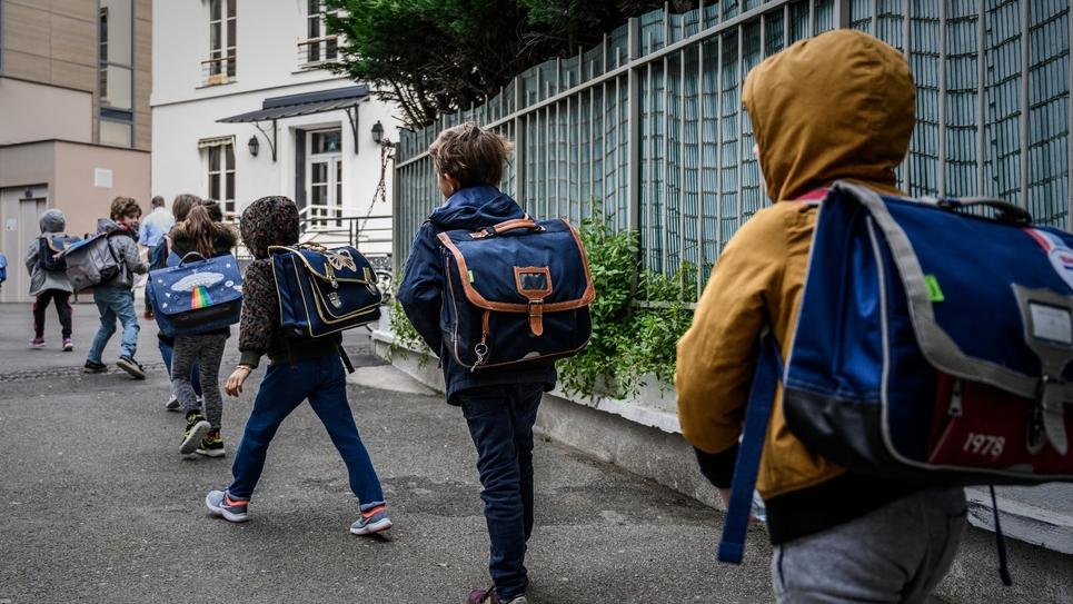 Des élèves se dirigent vers leur école en respectant une distance de sécurité, le 12 mai 2020 à Paris