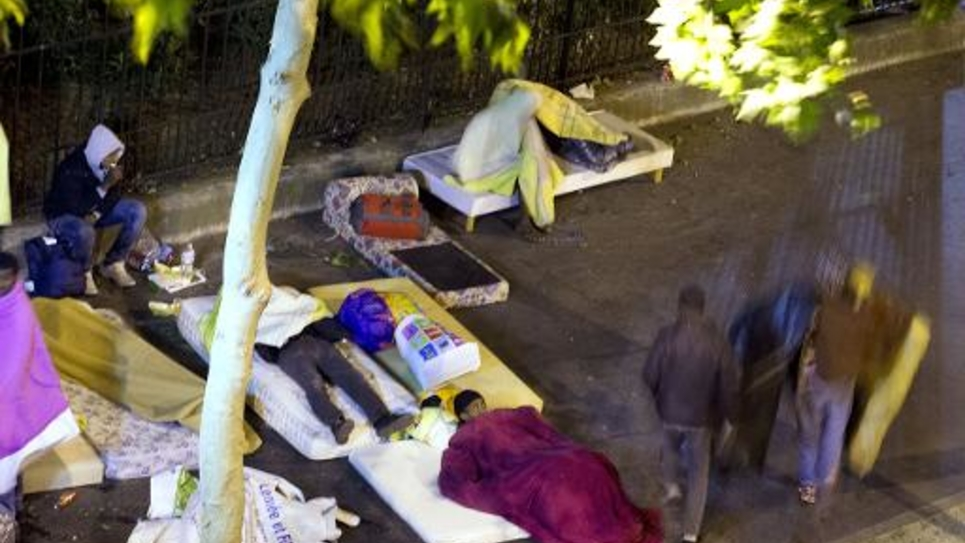 Des migrants installés le 8 juin 2015 avec des matelas dans un campement de fortune Place de Chapelle, dans le nord de Paris