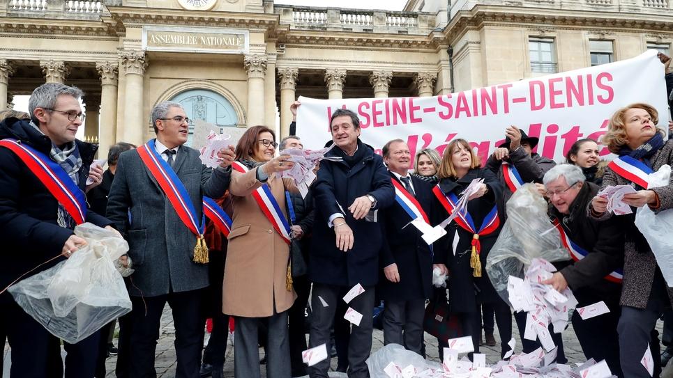 Des élus de Seine-Saint-Denis déversent des milliers de faux billets devant l'Assemblée nationale à Paris, le 19 décembre 2018