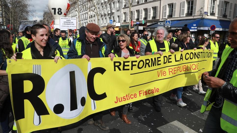 """Une banderole en faveur du R.I.C lors d'une manifestation de """"gilets jaunes"""", le 19 mars 2019 à Paris"""