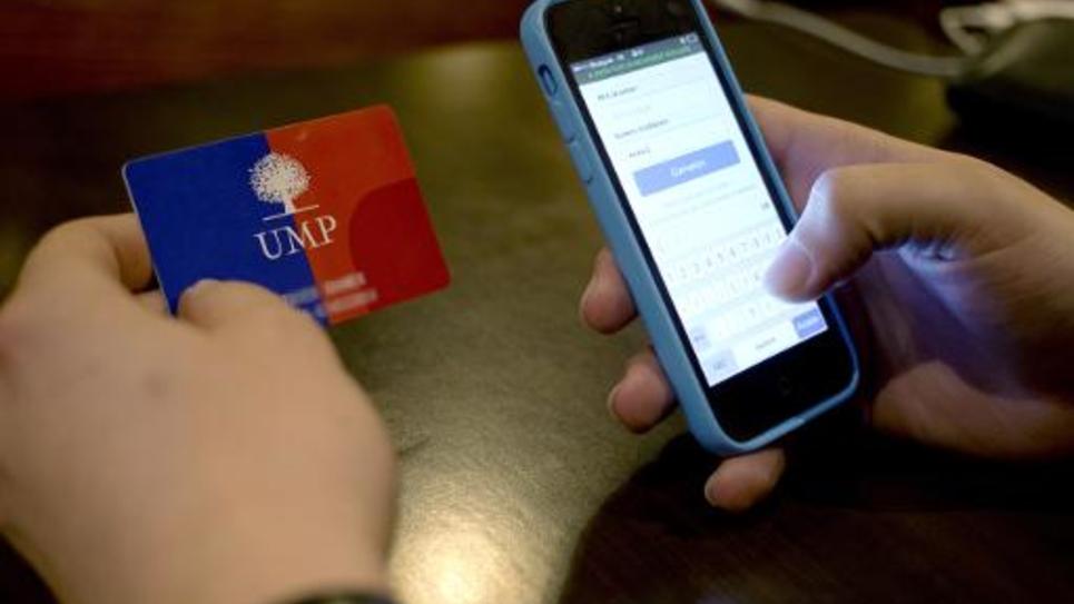 Un militant UMP utilise son smartphone, le 28 novembre 2014 depuis le siège du parti à Boulogne-Billancourt  pour voter et choisir le prochain président de l'UMP