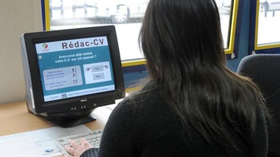 Une jeune femme rédige son CV dans une agence Pôle Emploi en 2011