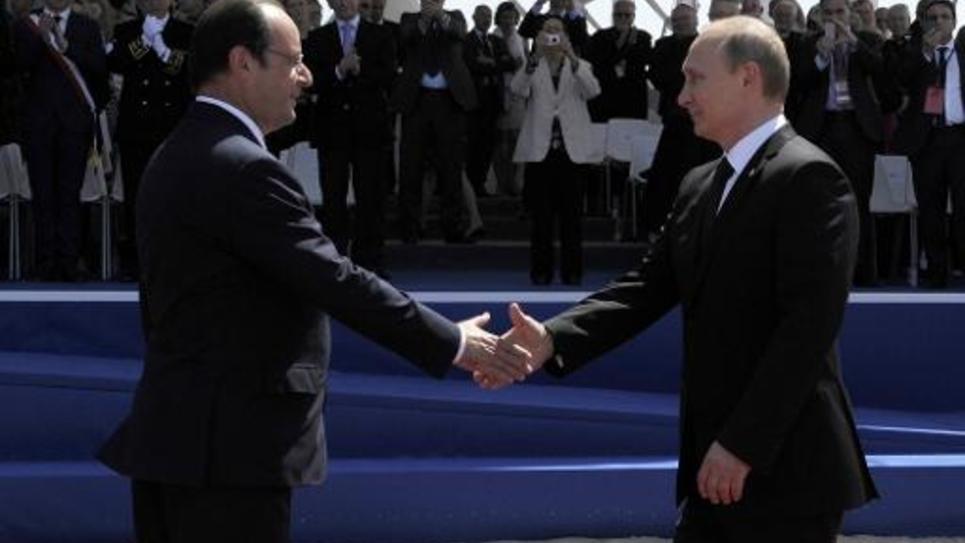 Le président français Francois Hollande (L) accueille le président russe Vladimir Poutine aux cérémonie de commémoration du Jour J à Ouistreham, en Normandie le 6 juin 2014, marquant le 70e anniversaire du débarquement allié