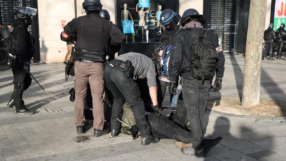 """Des policiers arrêtent un manifestant sur les Champs-Elysées, le 16 mars 2019 lors d'un samedi de mobilisation des """"gilets jaunes"""""""
