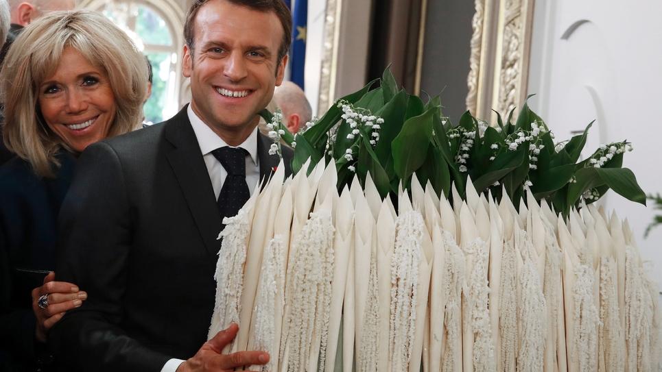 Le président Emmanuel Macron et sa femme Brigitte Macron à côté d'un bouquet de muguet lors d'une cérémonie à l'Elysée où étaient reçus les professionnels des métiers de bouche et des fleurs, le 1er mai 2019 à Paris