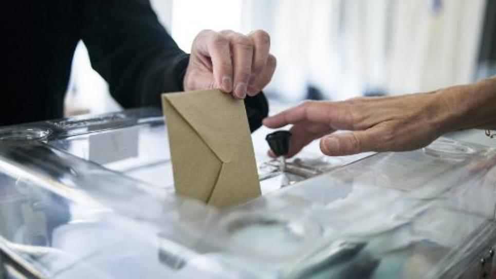 Une personne dépose son bulletin de vote dans une urne lors d'une élection en 2014 en France