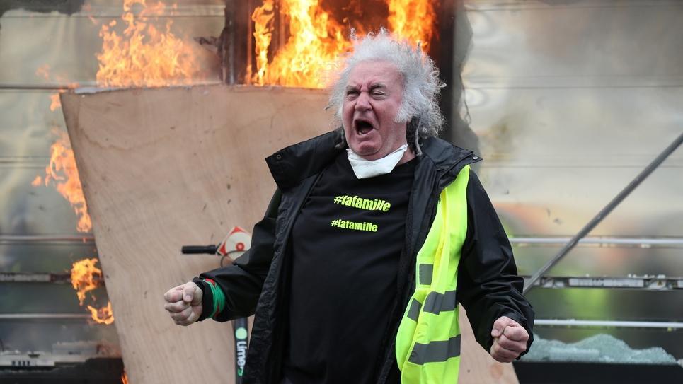 """Un """"gilet jaune"""" devant un kiosque à journaux en feu sur les Champs Elysées, à Paris, le 16 mars 2019"""