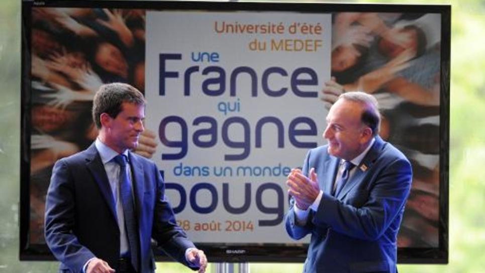 Le Premier ministre Manuel Valls applaudi par Pierre Gattaz à l'université d'été du Medef le 27 septembre 2014 à Jouy-en-Josas