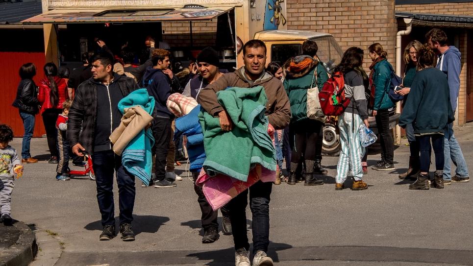 Des migrants reçoivent des couvertures données par une association près d'un gymnase où ils ont été hébergés après l'incendie du camp de Grande-Synthe, le 11 avril 2017