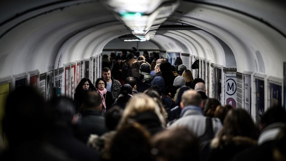 Des personnes font la queue dans un couloir du métro à la station Châtelet à Paris, au 8ème de grève dans les transports contre la réforme des retraites, le 12 décembre 2019