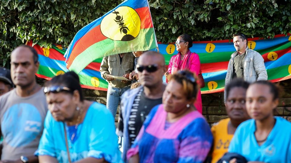 Une personne brandit le drapeau du FLNKS lors de la visite du président Emmanuel Macron en Nouvelle-Calédonie le 4 mai 2018 à Nouméa