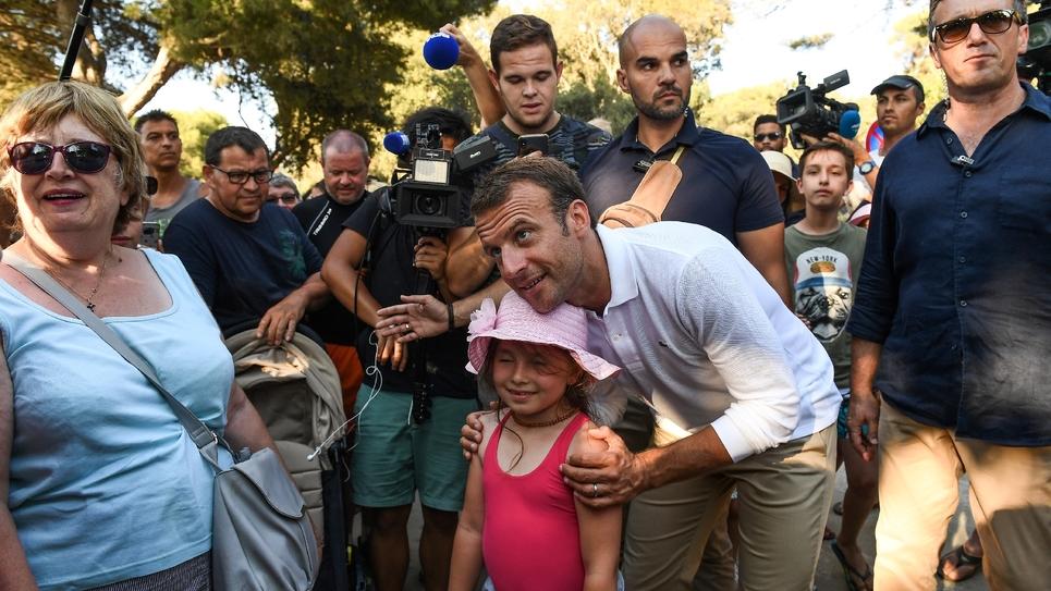 Emmanuel Macron pose pour les caméras lors d'un bain de foule le 7 août 2018 à Bormes-les-Mimosas, non loin du Fort de Bregancon, résidence d'été des présidents français