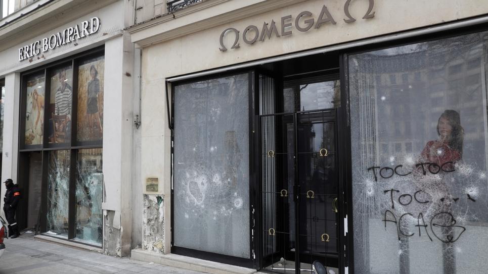 """Les vitrines brisées et taguées de boutiques sur les Champs-Elysées, au lendemain de la manifestation des """"gilets jaunes"""", le 17 mars 2019 à Paris"""