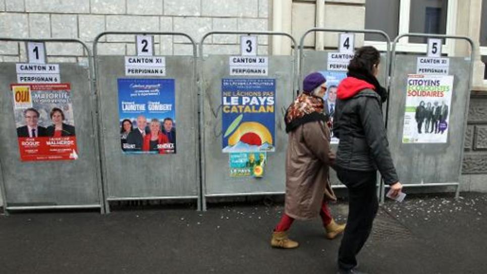 Des électeurs passent devant des affiches électorales, le 22 mars 2015 à Perpignan