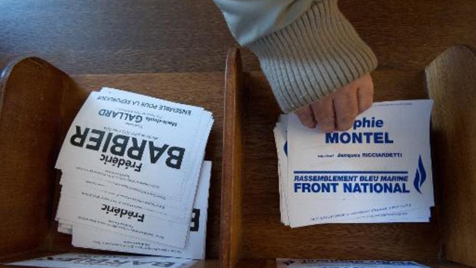 Une personne prend un bulletin de vote de la candidate du FN Sophie Montel, le 8 février 2015 à Pont de Roide
