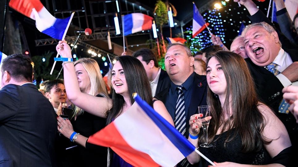 Des sympathisants du Rassemblement National (RN) réagissent à l'annonce des premiers résultats aux Européennes donnant le RN devant LREM, le 26 mai 2019 à Paris