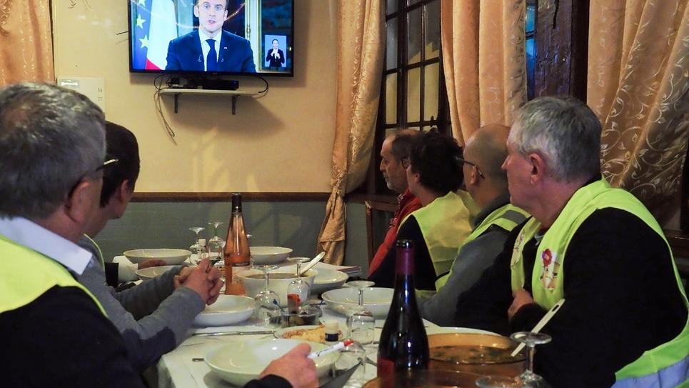 Des gilets jaunes regardent l'allocution télévisée d'Emmanuel Macron dans un restaurant à Fay-aux-Loges, le 10 décembre 2018