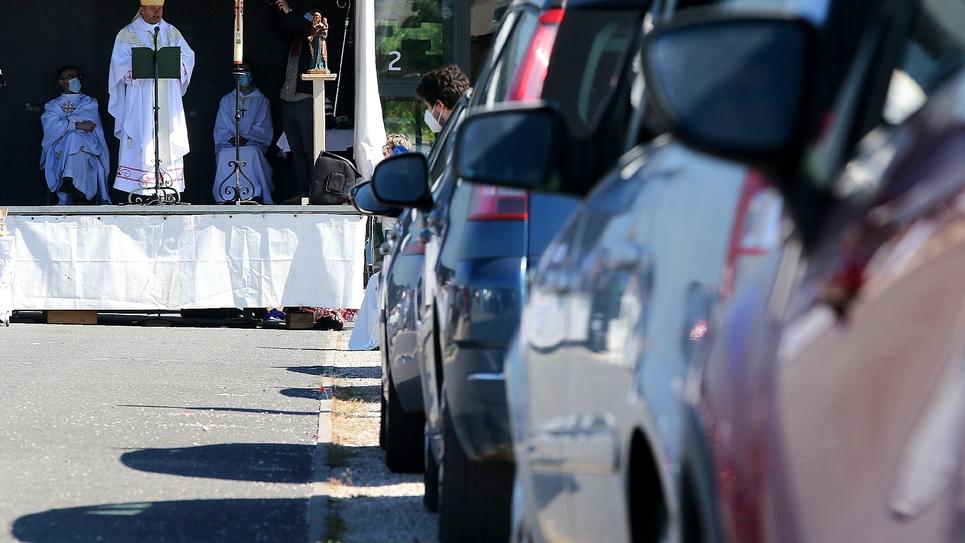 Des automobilistes garés sur un parking assistent à une messe en plein air célébrée par Mgr François Touvet, l'évêque de Châlons-en-Champagne, le 17 mai 2020