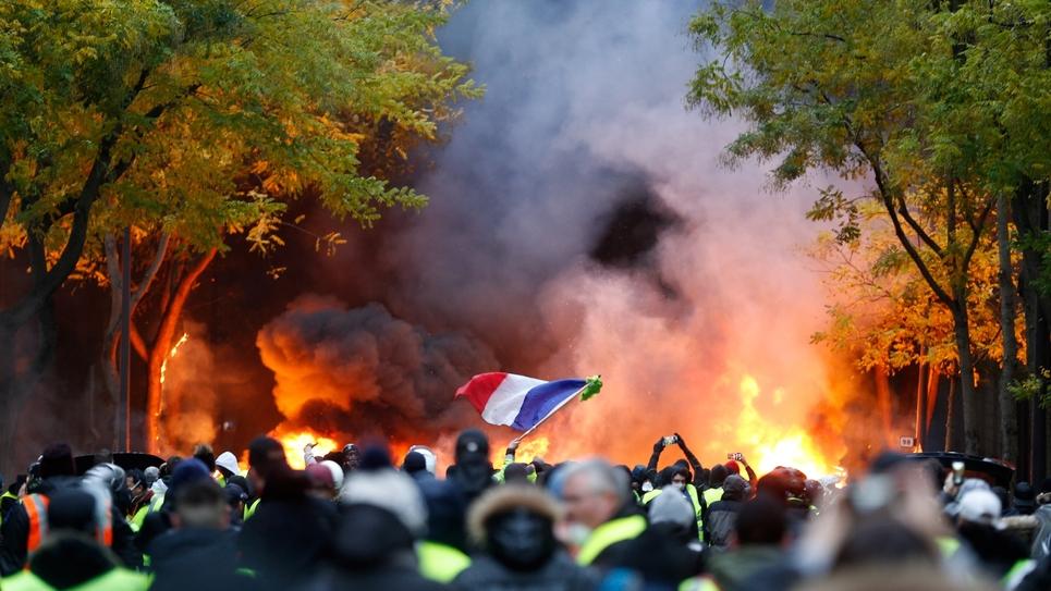 """Un drapeau français émerge d'une manifestation de """"gilets jaunes"""", le 1er décembre 2018 à Paris"""