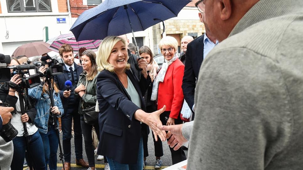 """La président du RN Marine Le Pen, présidente du Rassemblement National (RN), salue les gens alors qu'elle se rend au marché aux puces local """"braderie"""" le 8 septembre 2019 à Hénin-Beaumont, dans le nord de la France."""