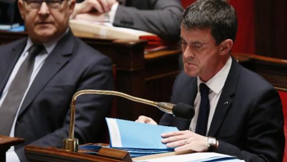 Le Premier ministre Manuel Valls (D) au côté du ministre des Finances Michel Sapin à l'Assemblée nationale le 11 février 2015 à Paris