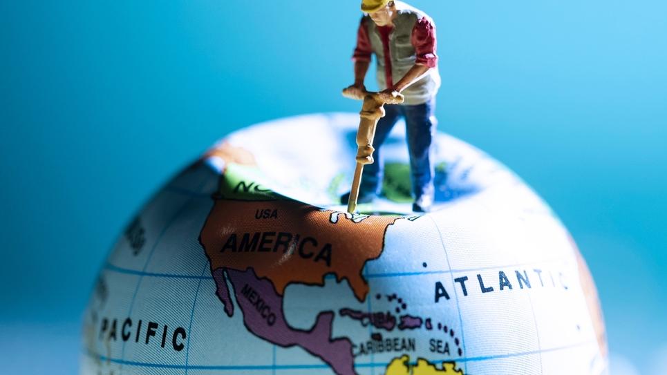 Illustration du 20 août 2018 avec la figurine d'un homme qui travaille avec un marteau-piqueur sur un globe terrestre