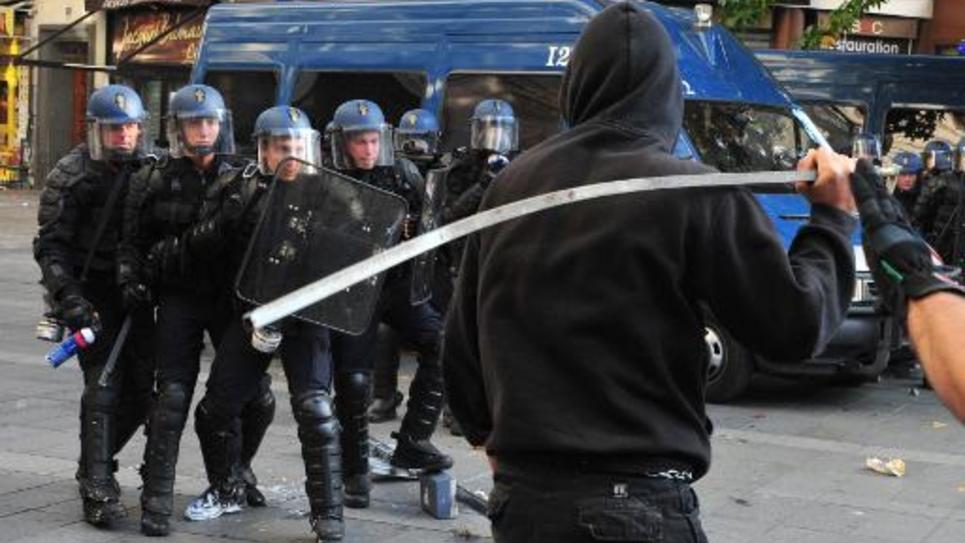 Un manifestant armé d'une barre de fer fait face aux gendarmes mobiles lors de violences en marge d'un rassemblement à la mémoire de Rémy Fraisse à Nantes le 1er novembre 2014
