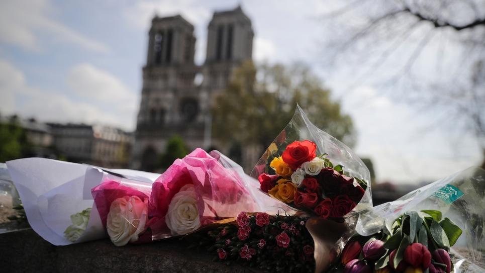 Des fleurs déposées sur le Pont Saint Michel, devant Notre-Dame, deux jours après l'incendie qui a ravagé la cathédrale, le 17 avril 2019
