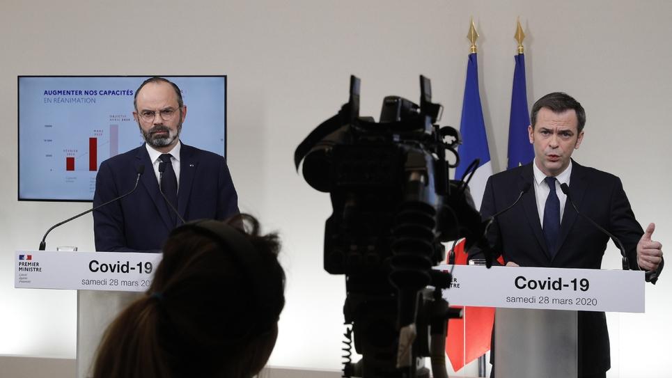 Le ministre de la Santé Olivier Veran (D) et le Premier ministre Edouard Philippe lors d'une conférence de presse conjointe, le 28 mars 2020 à Paris